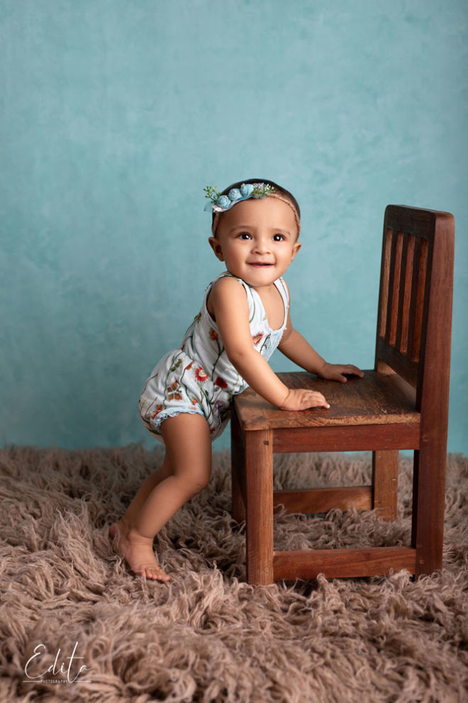 Smiling and cute baby girl standing with support holding chair