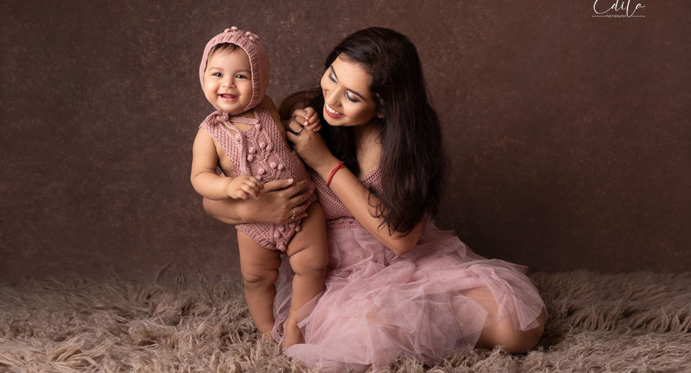 Mummy and her daughter in pink outfits on brown background