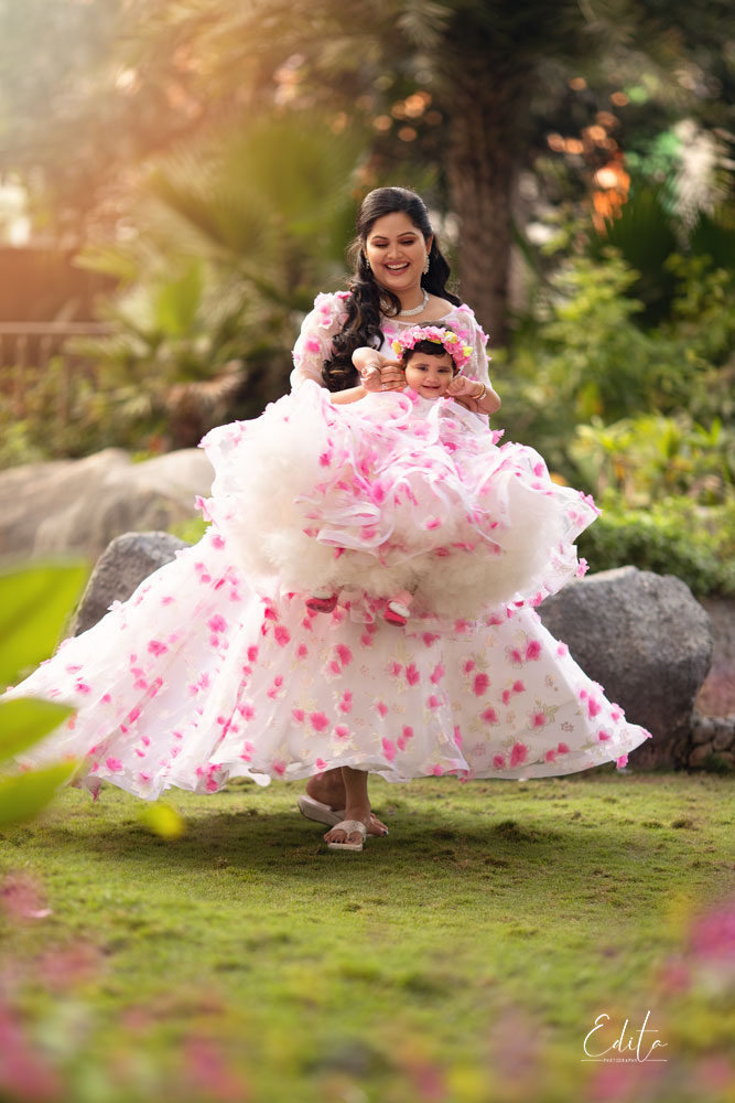 Mother and daughter in matching outfits playing in garden in Pune