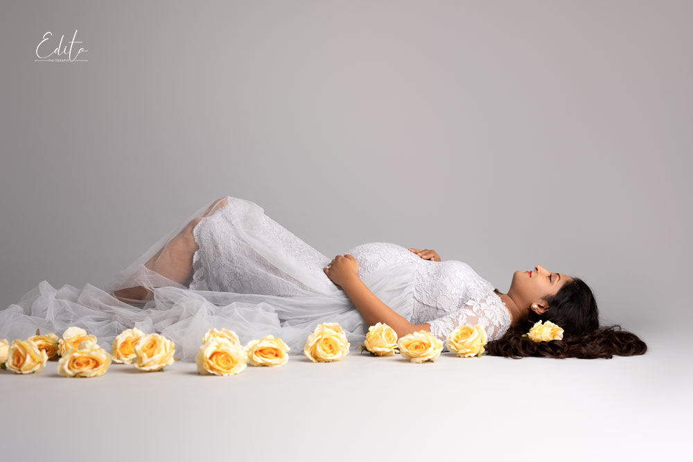 Pregnant mom to be i grey gown lying down at studio