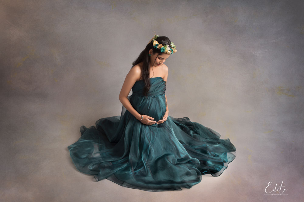 Pregnant woman in green outfit sitting and looking at her belly