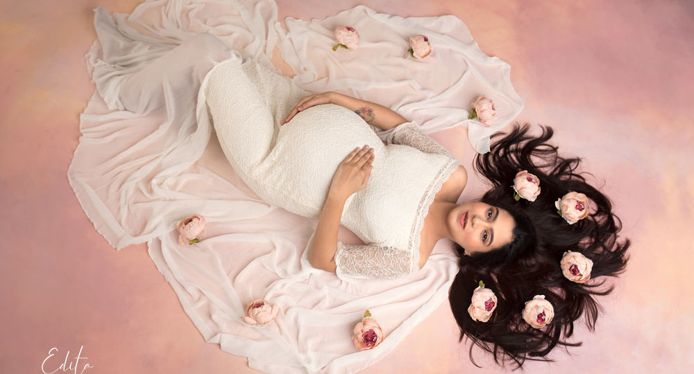 Aerial maternity photo in white gown on pink purple and yellow background