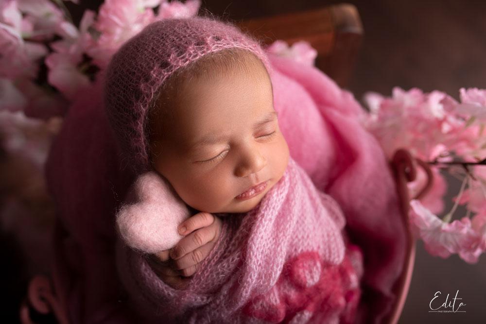 Newborn in pink bucket holding heart in her hands