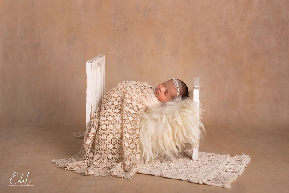 newborn baby in small bed in beige