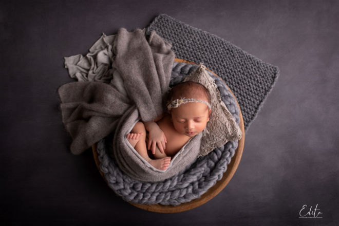 Newborn baby girl in grey wooden bowl setup