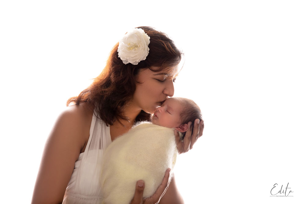 Mom is kissing her newborn daughter, back light photo