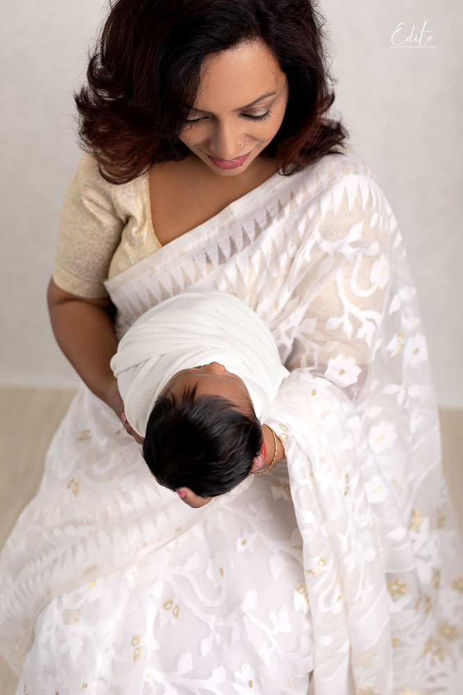 Indian mother in white sari is holding her newborn son in Pune