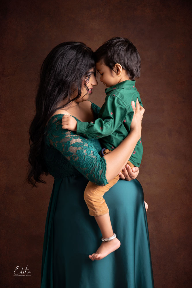 Pregnant mother in green outfit is holding her 3 year old son on her belly