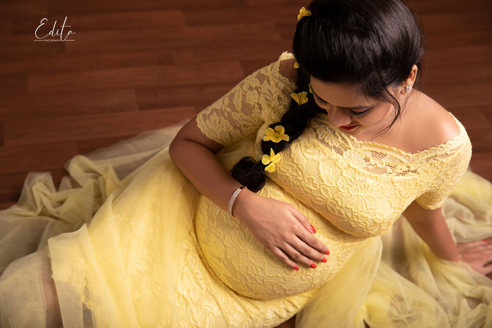Pregnant woman in yellow gown siting and looking at her belly in Pune