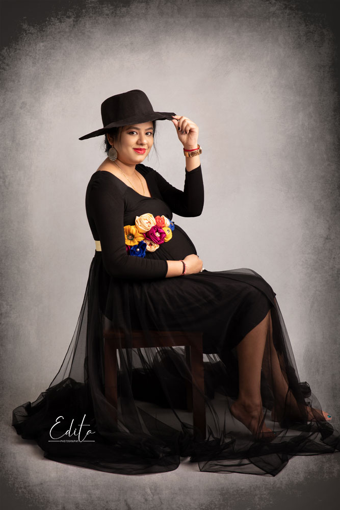 Maternity photography - mom to be in black gown and black hat sitting on chair