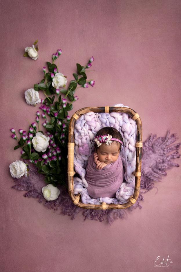 10 days indian newborn baby girl in purple setup in bamboo basket