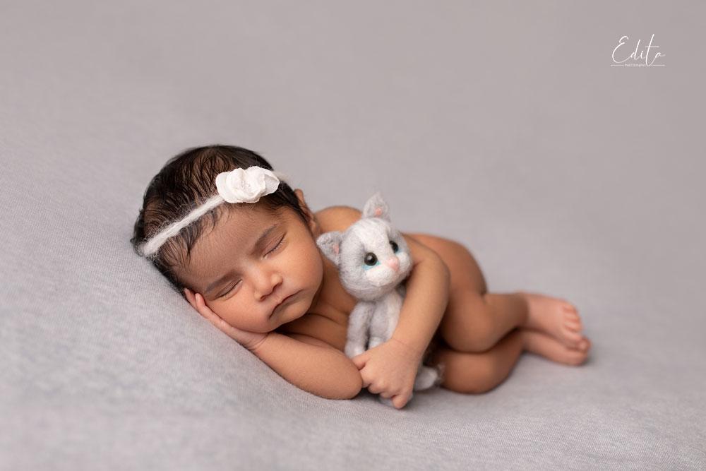 Newborn on side pose holding cute kitten