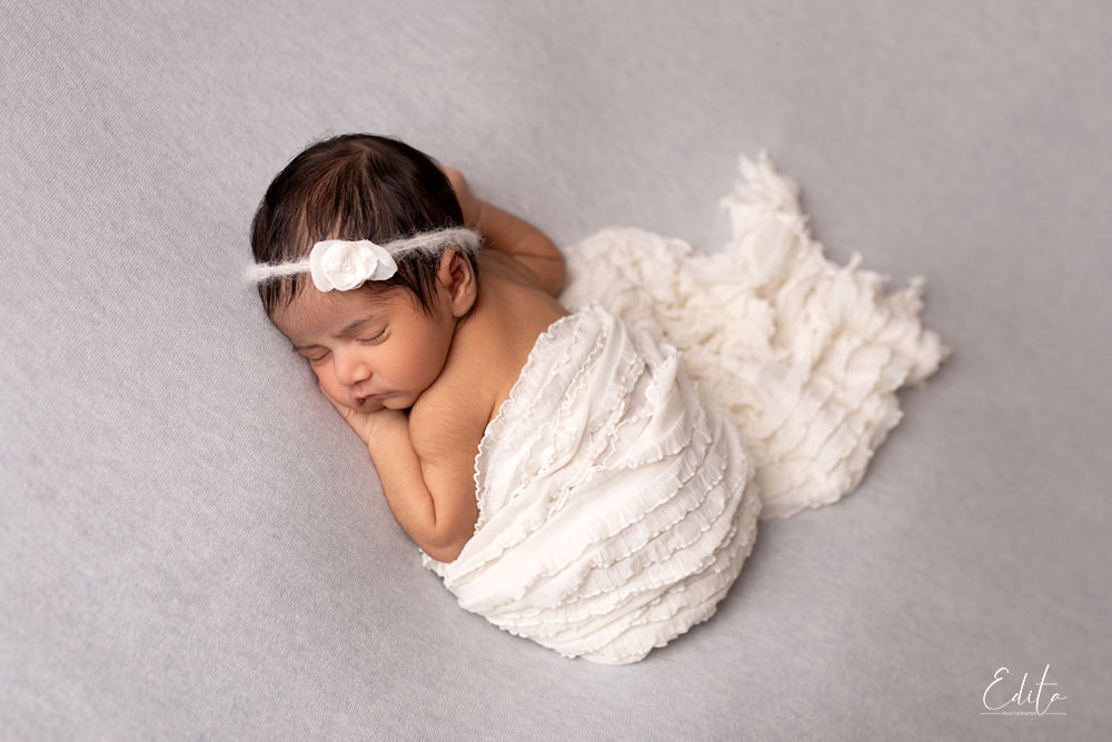 Newborn bum up pose with white wrap on grey background