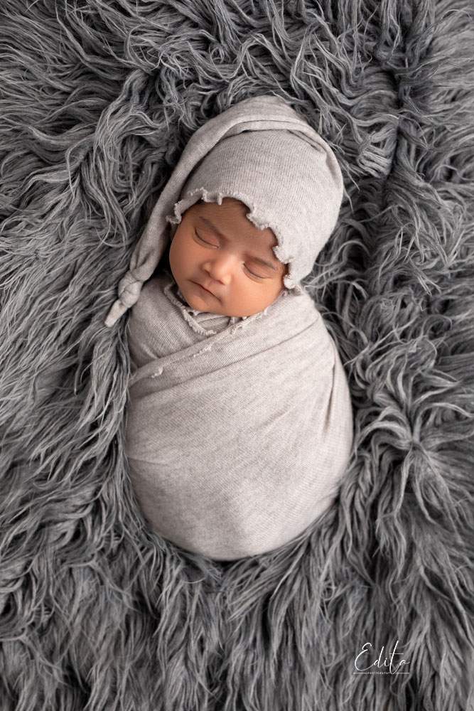 Newborn wraped in grey wrap and with grey hat
