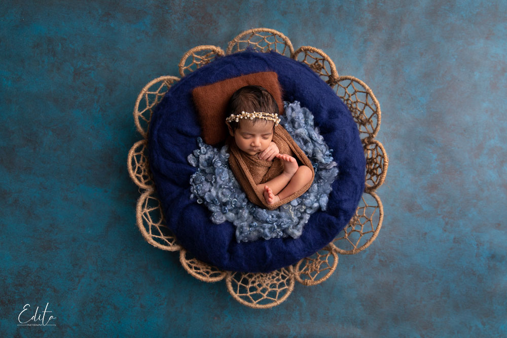 indian baby girl in blue and brown setup posed in basket