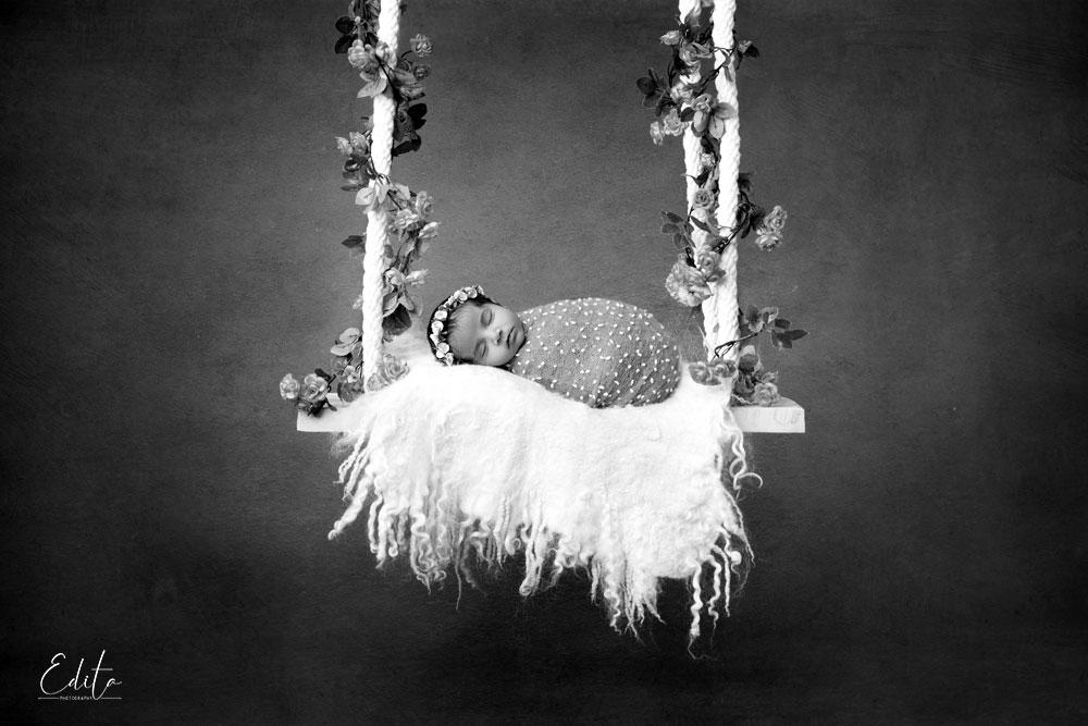 newborn baby on swings black and white