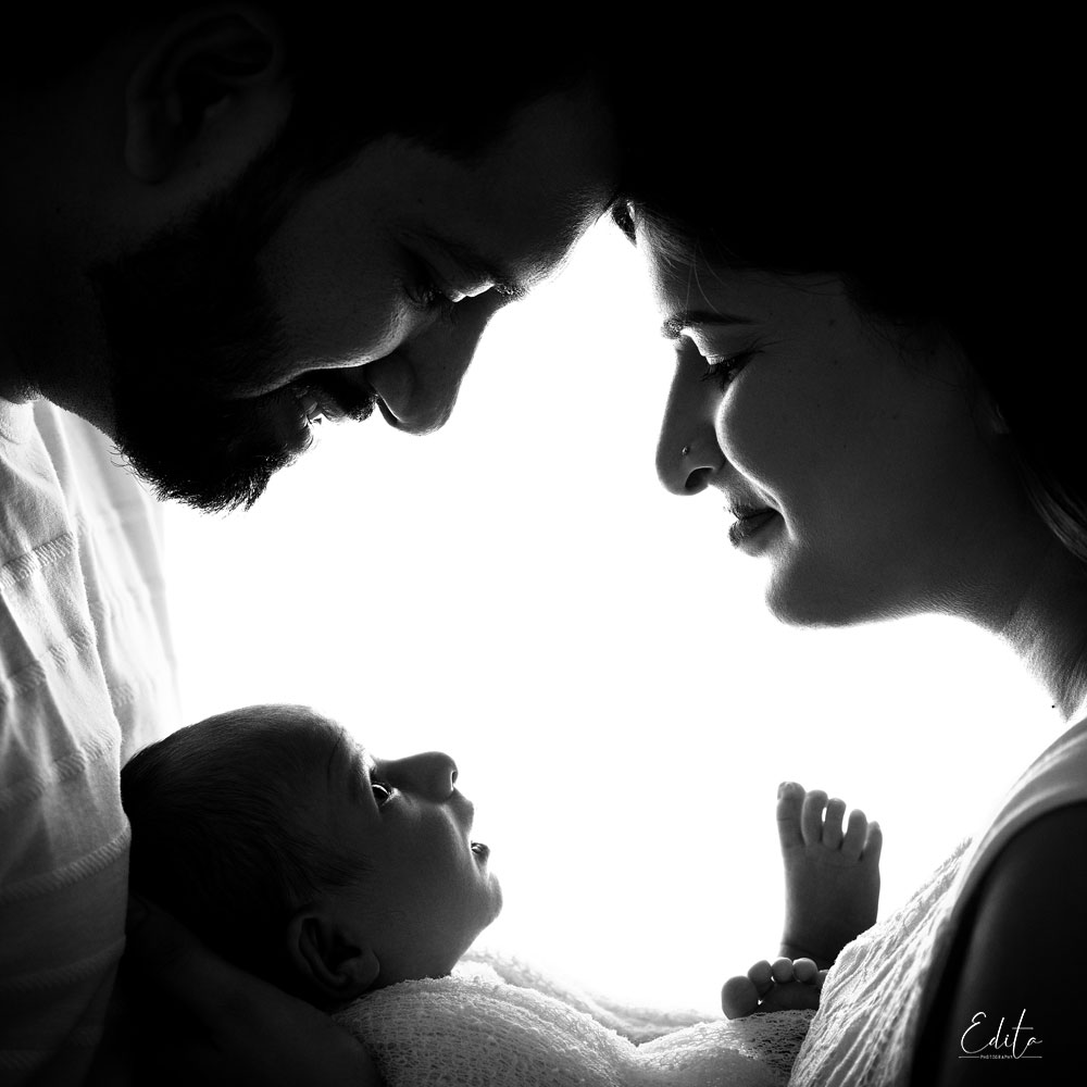 Silhouette newborn baby with parents
