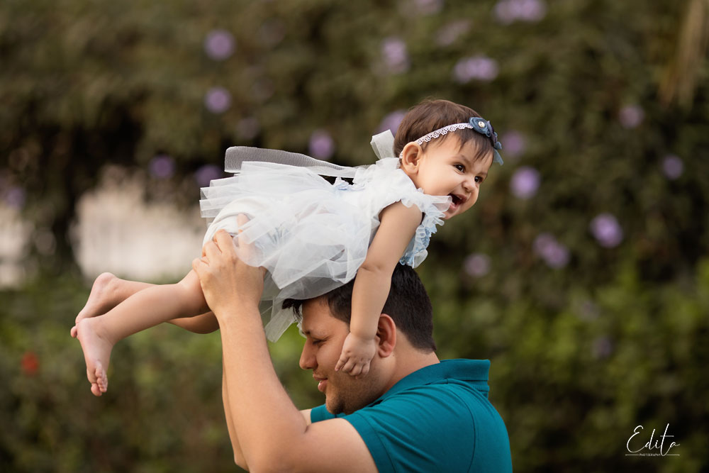 Dad is holding daughter baby on his head photoshoot