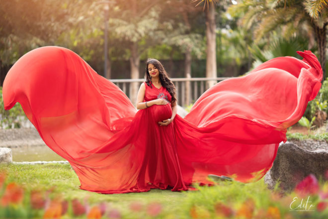 Maternity photography in red flying gown