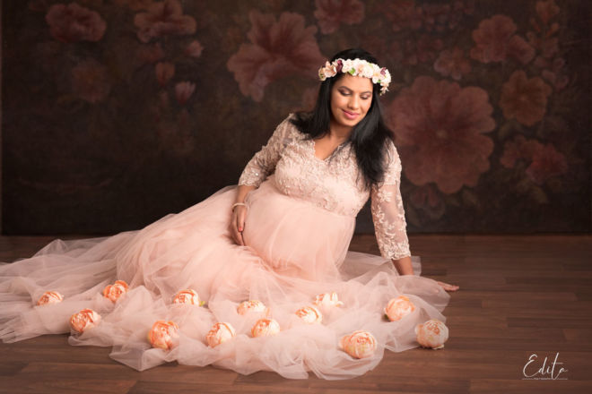 Pregnancy photography poses at studio in peach gown