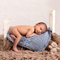 Newborn baby posed on tiny bed prop