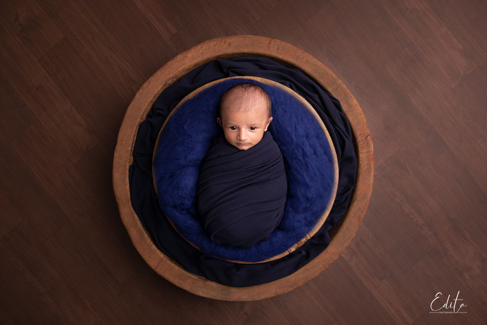 Newborn baby in blue posed in wooden bowl
