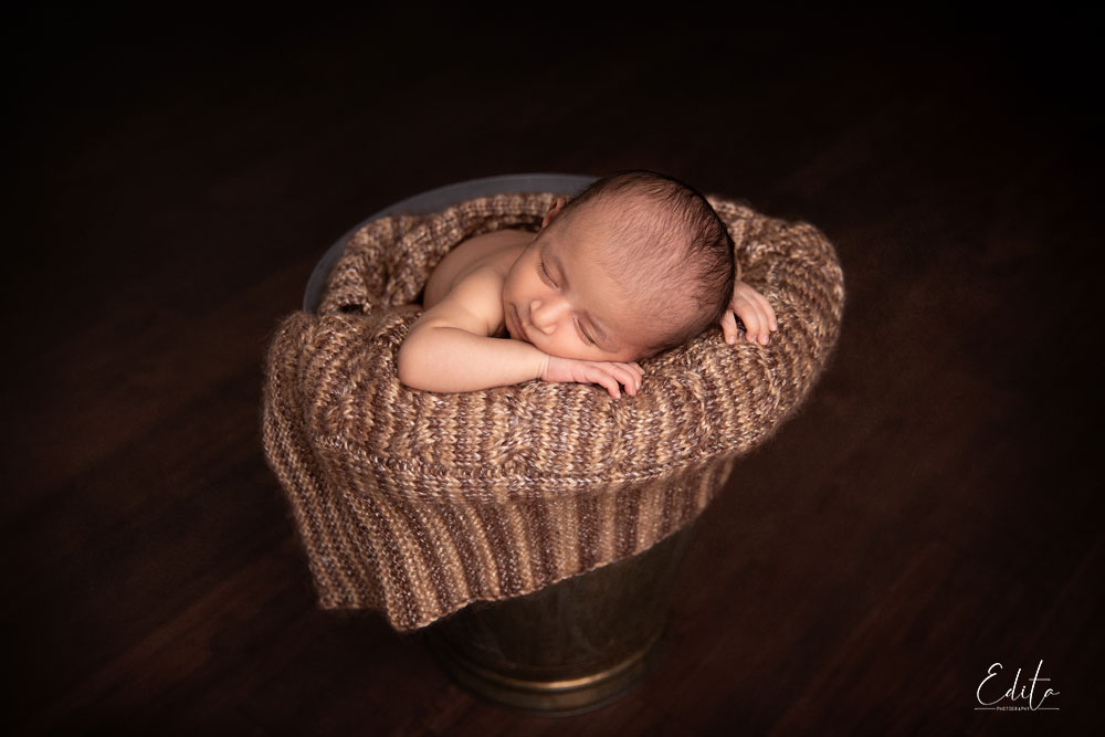 Newborn baby posed in bucket in brown colors