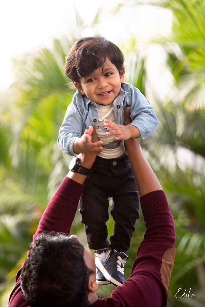 Father holding baby boy high in air photo in garden in Pune
