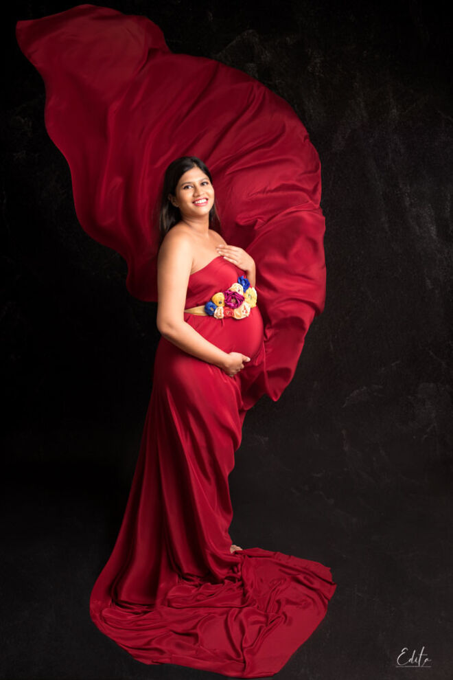Red fabric tossing in pregnancy photoshoot in Pune
