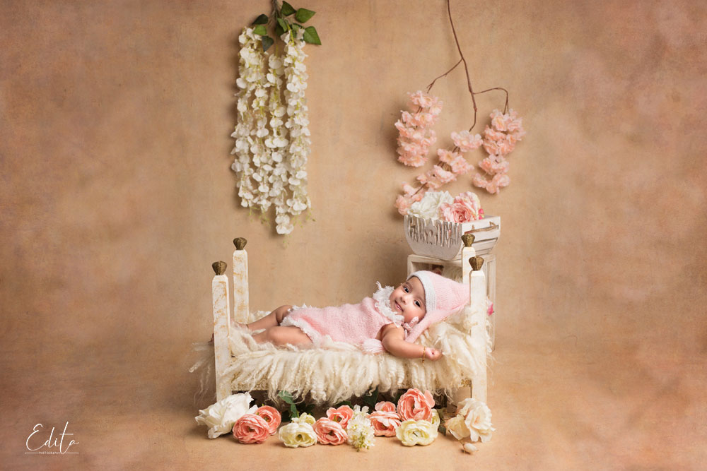 3 month baby girl on tiny bed decorated setup with flowers