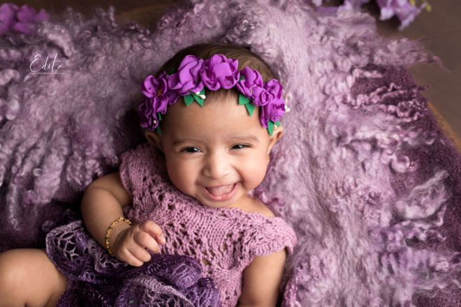3 month old baby girl in purple setup with headband and big smile