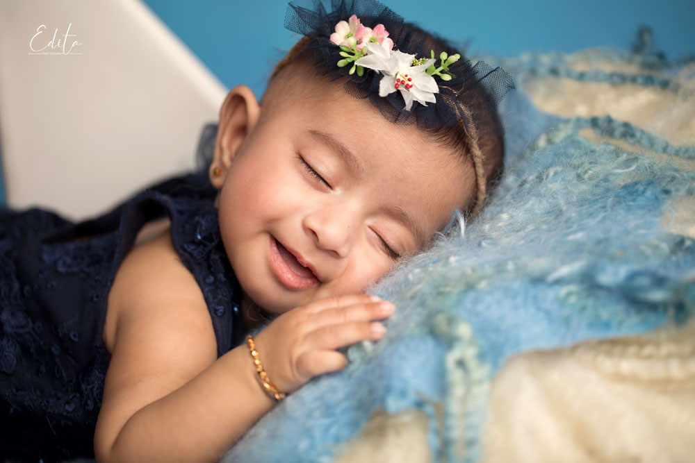 Smiling 3 month indian baby in navy blue dress