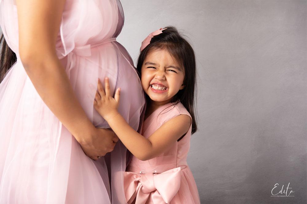 Elder daughter - big sister with her pregnant mom belly