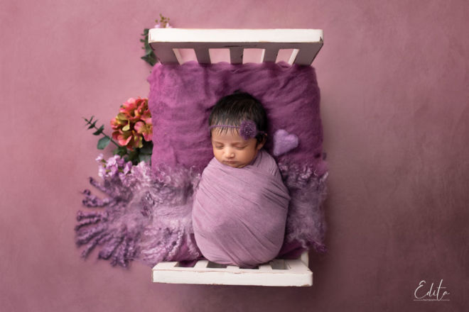 Newborn baby girl photography ideas in tiny bed purple setup