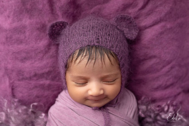 Smiling 2 weeks baby girl with purple hat photo