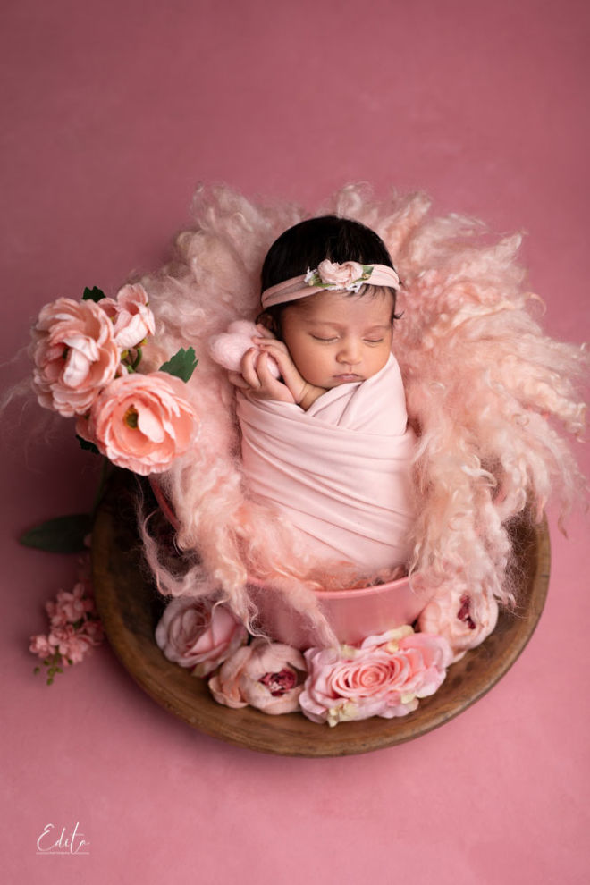 Baby girl posed in pink bucket with flowers around photoshoot ideas