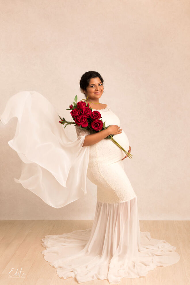 Pregnancy photos with red roses and white gown