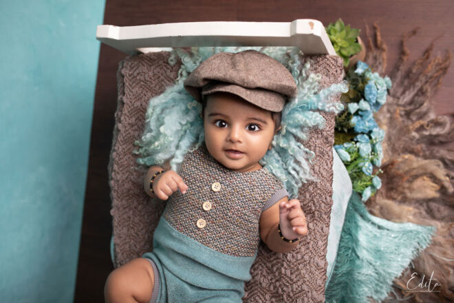 Baby boy photo shoot with cap on small bed prop by Edita Photography