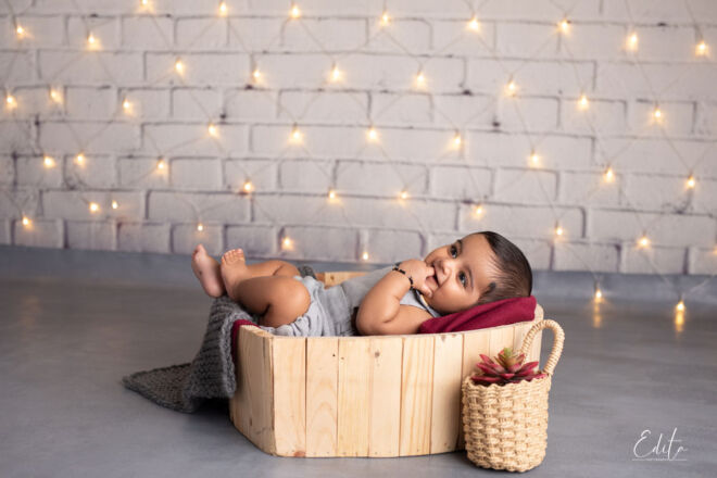 Baby boy photo shoot in heart shaped bowl with christmas lights in background