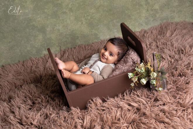 Baby photo shoot in brown bed prop