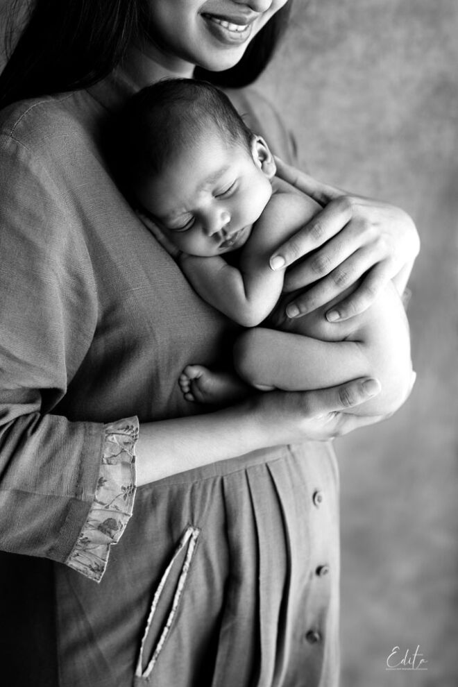 Mother is holding newborn baby boy black and white photo shoot