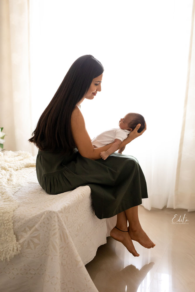 Mom sitting on bed and holding newborn baby girl backlit photo