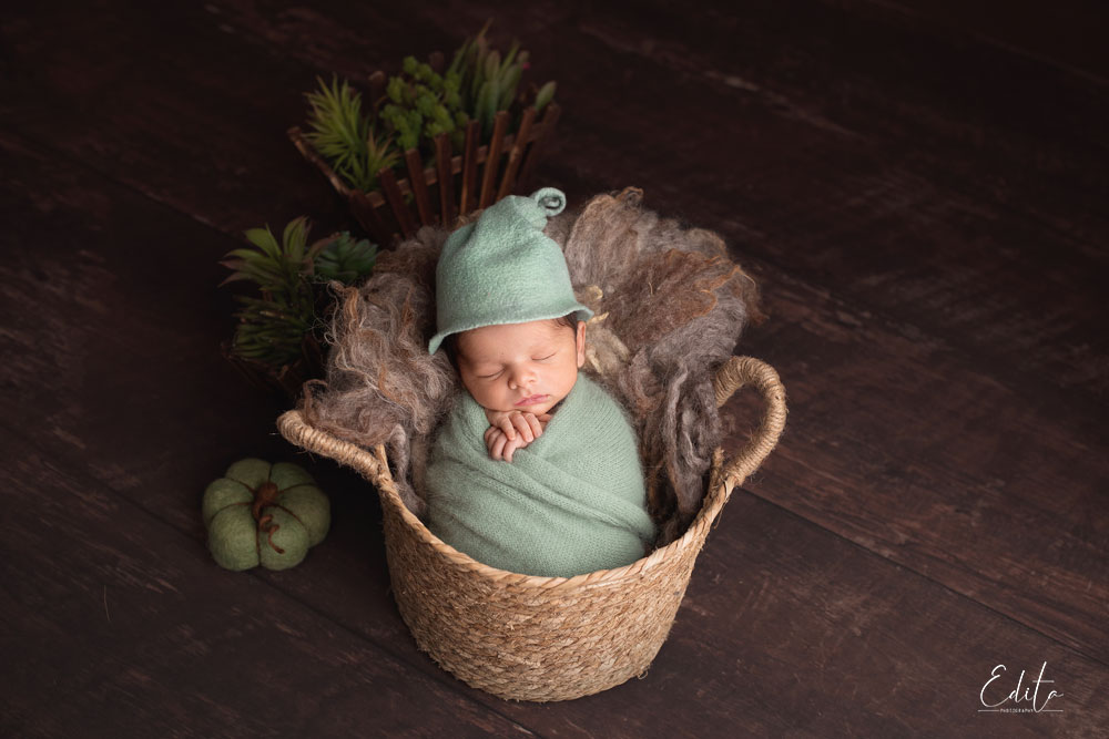 15 days baby photography in green wrap posed in jute basket