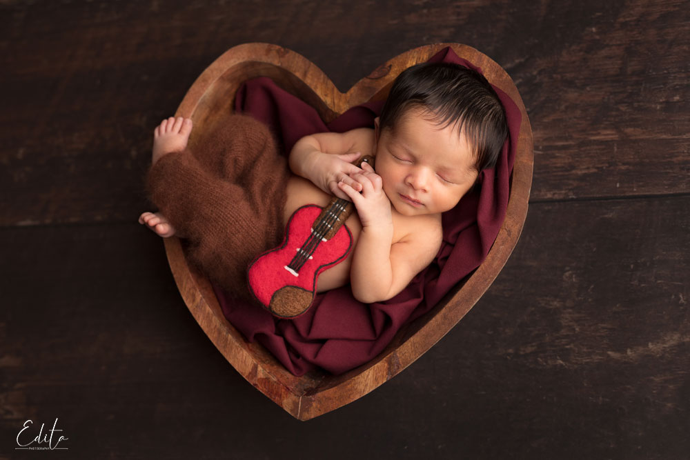 Newborn boy in heart shaped bowl with guitar brown and red setup