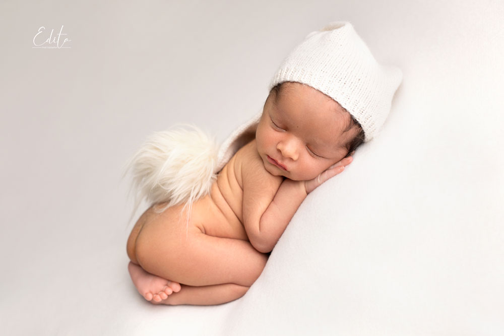 15 days baby photoshoot on tummy with hat on bean bag