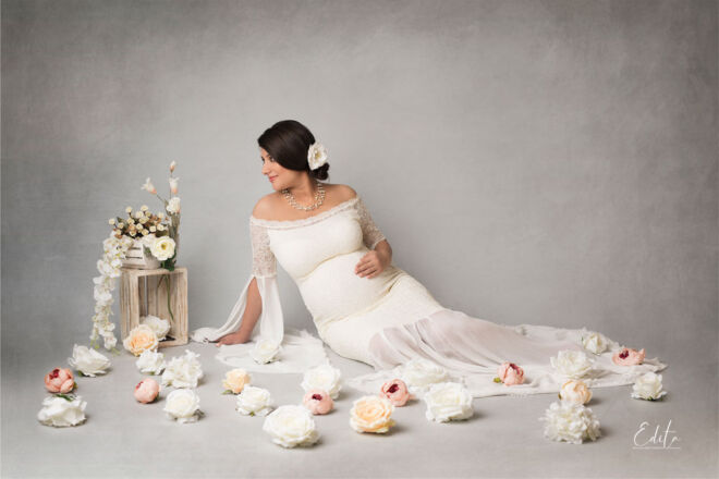 Pregnancy photoshoot in Pune in white gown sitting between the flowers