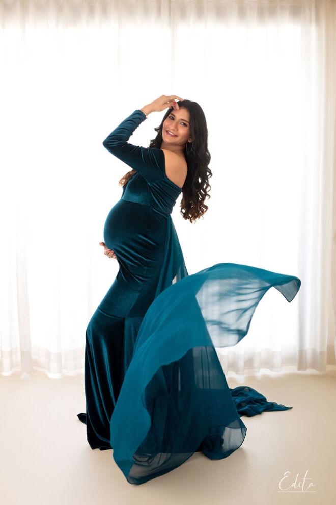 Maternity backlit photo in blue velvet gown at studio