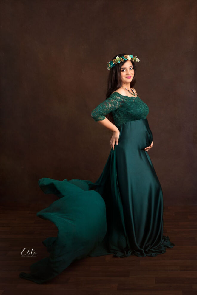 Pregnancy photo shoot in green gown and brown background at studio in Pune