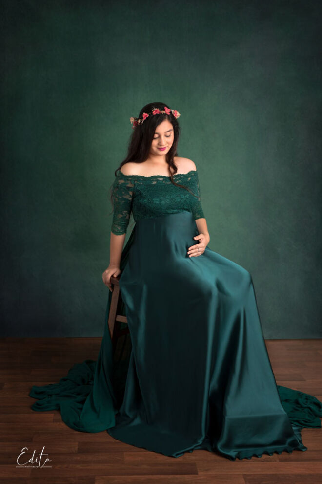 Maternity posing on high chair, green emerald gown on green matching background canvas