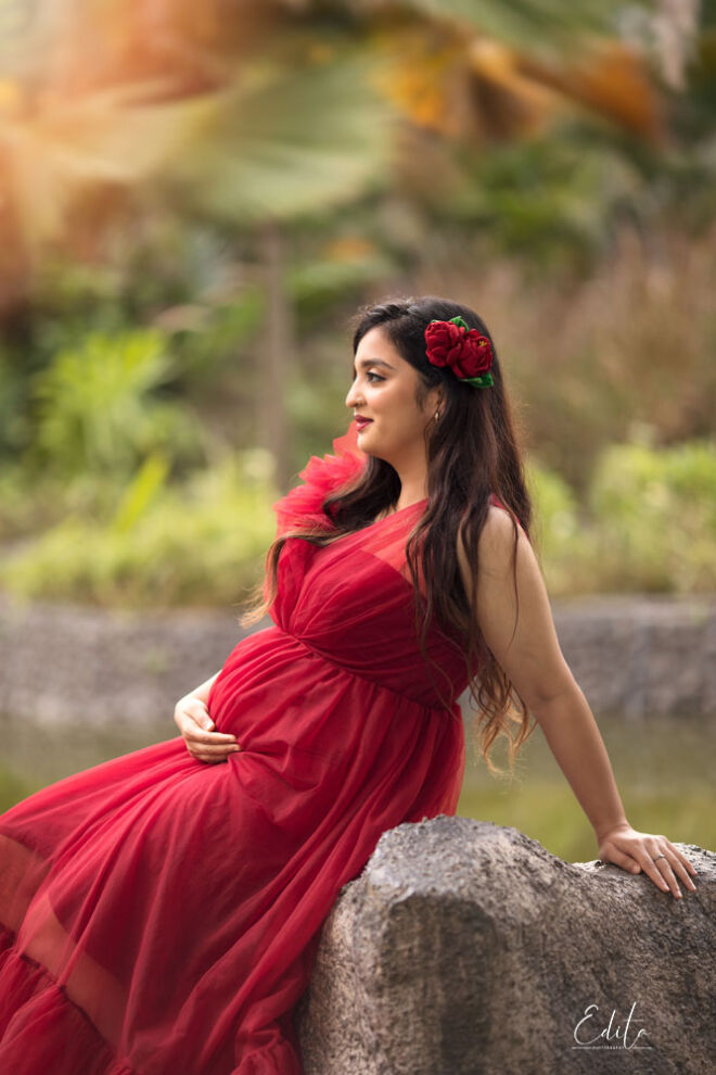 Pregnant woman in red gown is sitting on the rock backlit sunset time photo